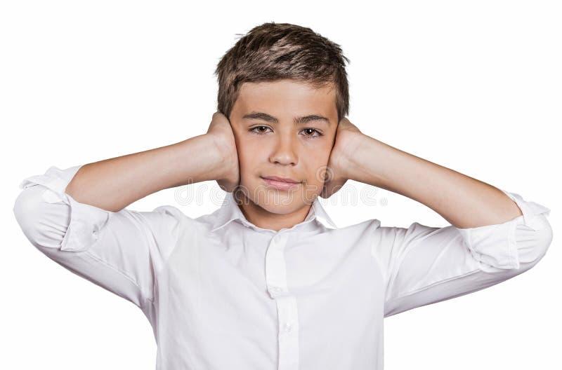 男孩覆盖物耳朵用手,不要听见喧闹声,忽略交谈 库存照片
