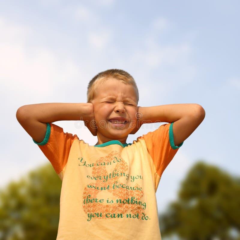 男孩覆盖物耳朵递他的年轻人 免版税库存照片