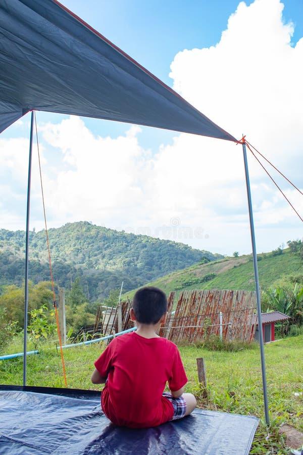 男孩观看山和天空在帐篷 库存图片