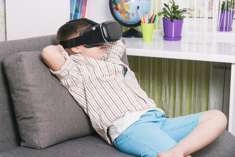 男孩观看有虚拟现实玻璃的录影,户内 数字式虚拟现实设备 免版税库存照片