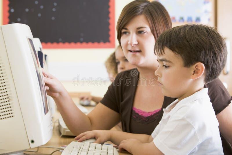 男孩计算机他的教师工作 库存照片