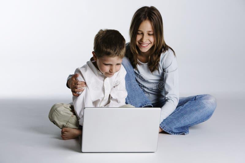 男孩计算机女孩愉快的膝上型计算机 图库摄影