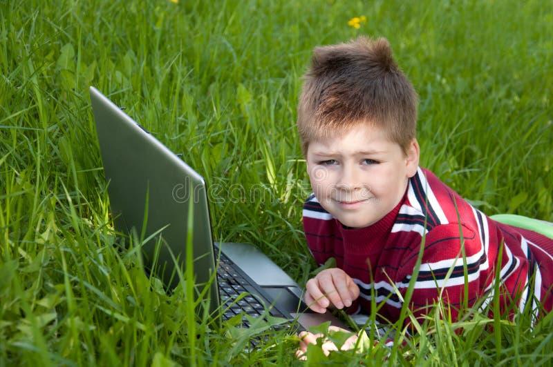 男孩计算机草膝上型计算机位于 图库摄影