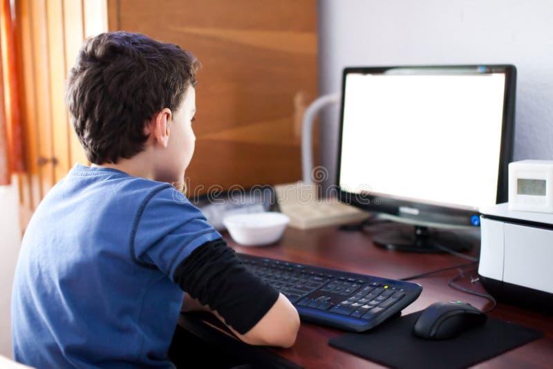 男孩计算机读取屏幕 免版税库存照片