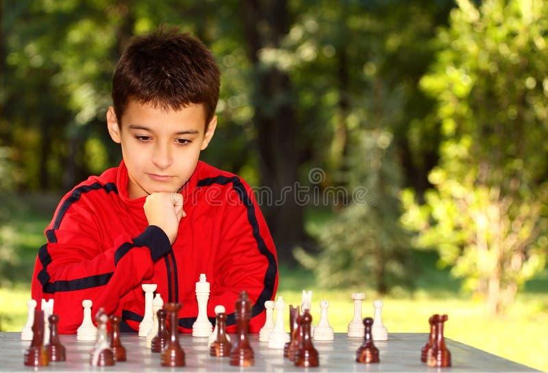 男孩认为的一盘象棋 库存照片