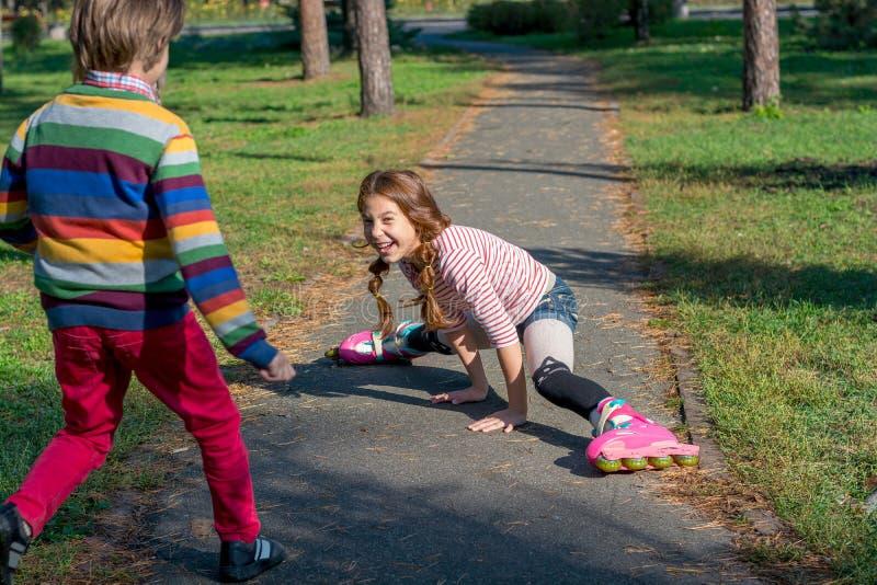 男孩赶紧帮助跌倒的女孩,滚动在路辗 免版税库存照片