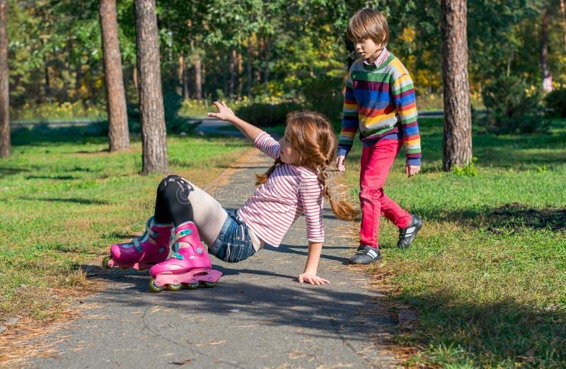 男孩赶紧帮助跌倒的女孩,滚动在路辗 库存照片
