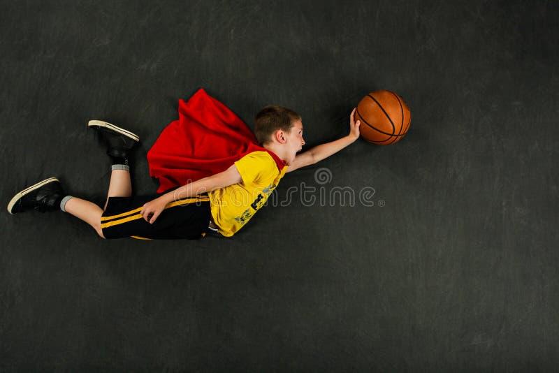 男孩超级英雄蓝球运动员 免版税库存照片