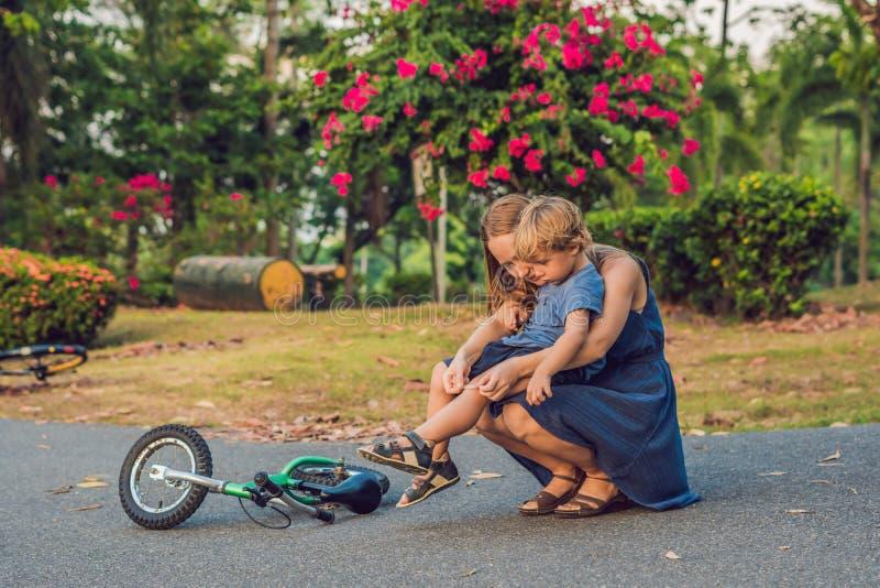 男孩跌下自行车,他的母亲浆糊在他的膝盖的膏药 库存照片