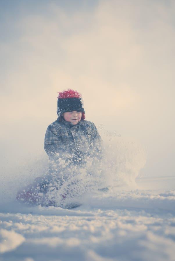 年轻男孩跑尖叫在他的在小山下的雪橇 免版税库存图片