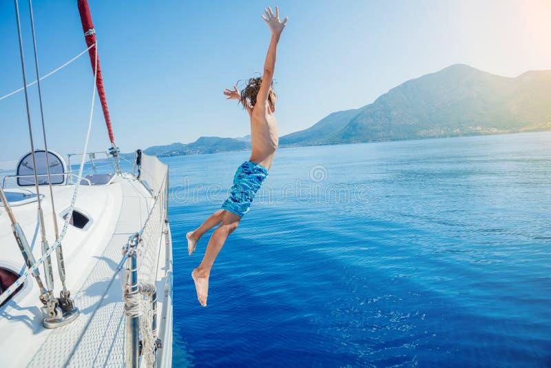 男孩跳在夏天巡航的航行游艇 旅行冒险,乘快艇与孩子 库存照片