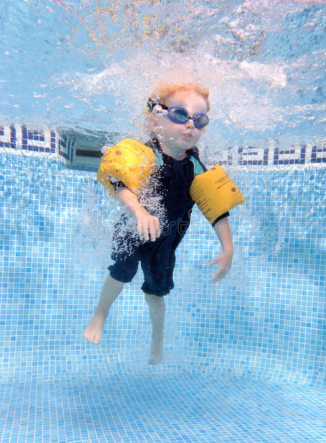 男孩跳的池游泳年轻人 图库摄影