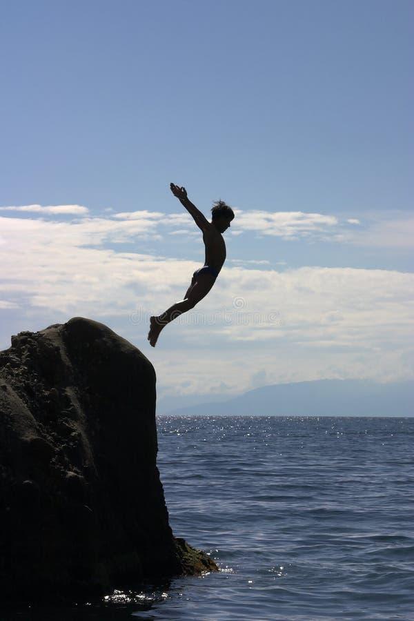 男孩跳的海运 免版税库存照片