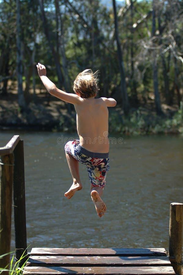 男孩跳的湖 免版税库存照片