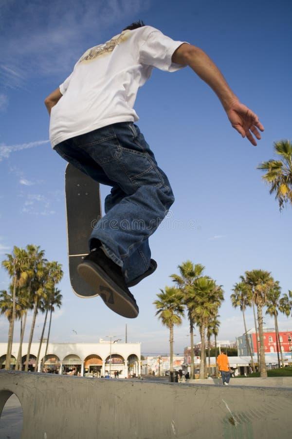 男孩跳的踩滑板青少年 库存图片