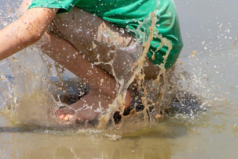 男孩跳进混乱肮脏的水 库存图片