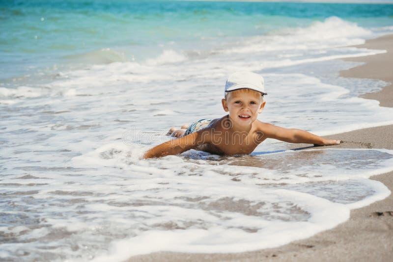 男孩躺在沙滩上 免版税库存照片