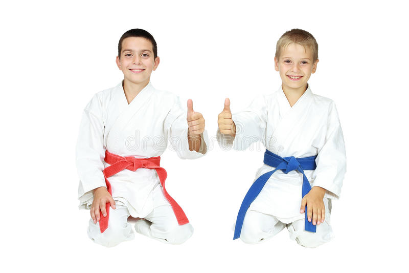 男孩运动员在礼节姿势空手道坐并且指向超级的手指 免版税库存图片