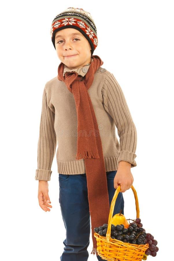 男孩运载的篮子用葡萄 免版税库存图片