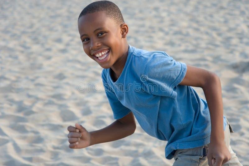 男孩连续沙子微笑 库存图片
