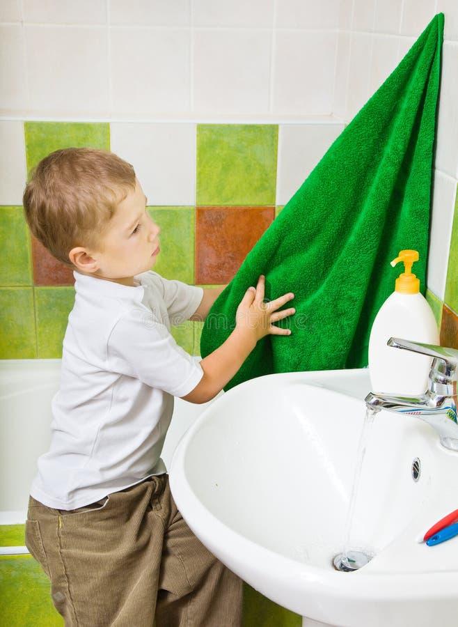 男孩递特里毛巾洗涤物抹 免版税库存图片