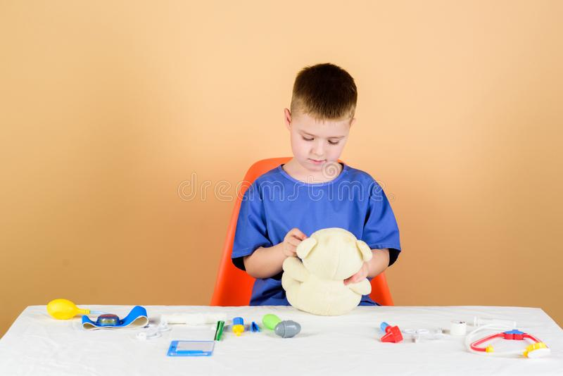 : 男孩逗人喜爱的儿童未来医生事业 E 繁忙孩子小的医生坐与医疗工具的桌 库存图片