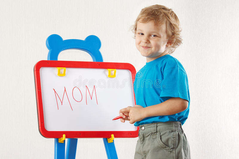 男孩逗人喜爱的矮小的妈妈微笑的字写道 免版税库存照片