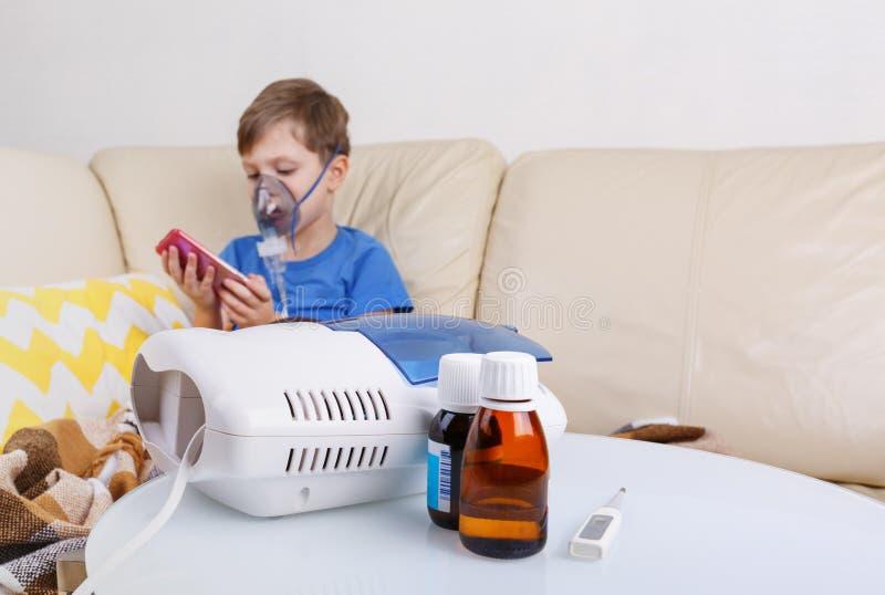 男孩通过雾化器呼吸 与小儿科雾化器的病态的chid 库存照片