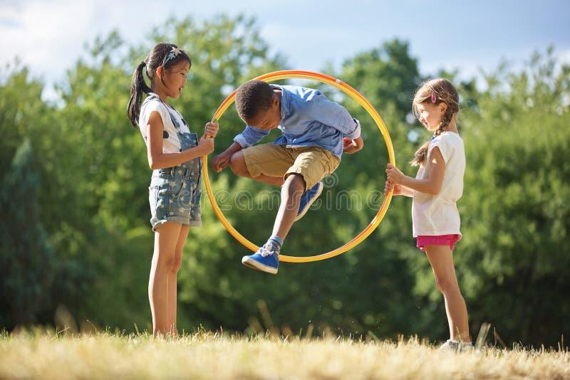 男孩通过hula箍跳 免版税库存照片