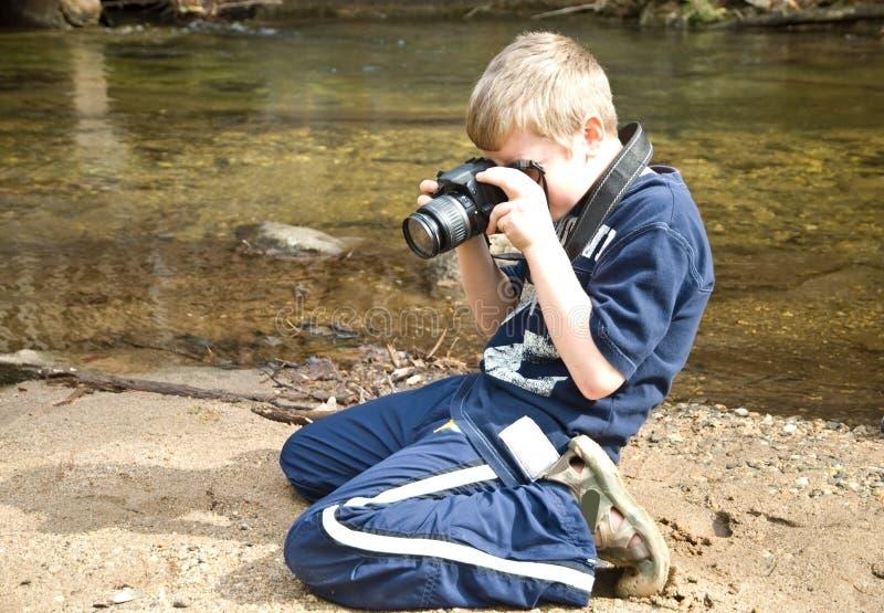 男孩采取年轻人的照相机照片 免版税库存照片