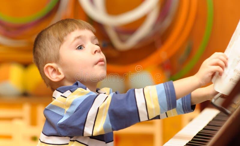 男孩钢琴作用 库存图片