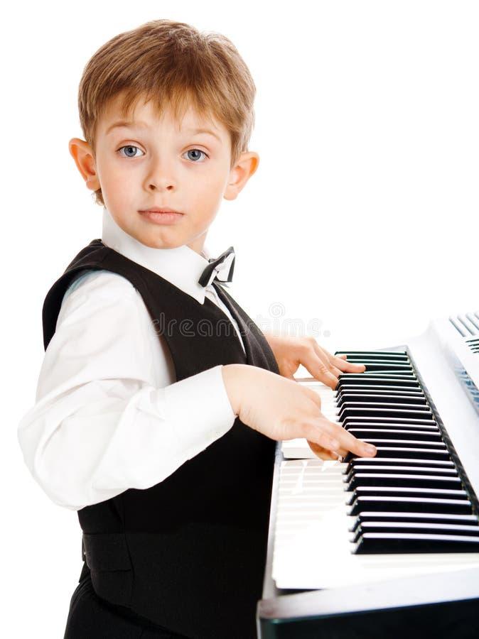 男孩钢琴使用 库存图片
