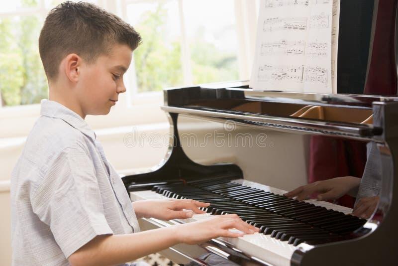 男孩钢琴使用 免版税库存图片