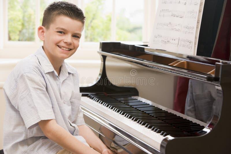 男孩钢琴使用 免版税库存照片