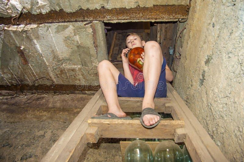男孩长期拿着有蔬菜和水果的瓶子在地下室用食物,存贮的 库存图片