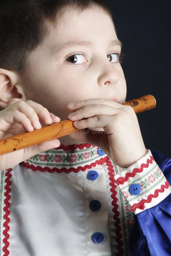 男孩长笛一点使用木 图库摄影