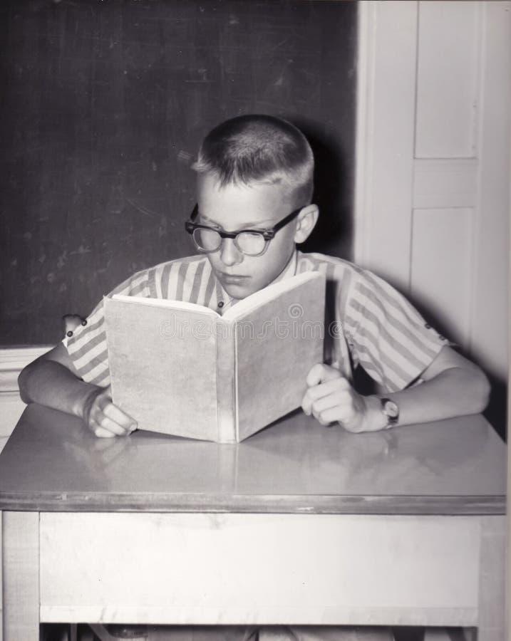 年轻男孩阅读书葡萄酒照片  免版税图库摄影
