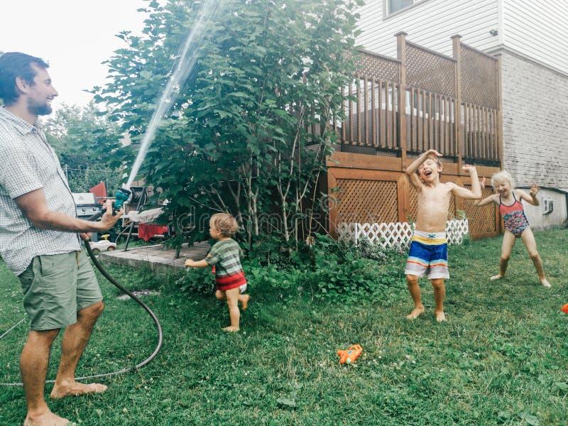 男孩飞溅使用的女友兄弟姐妹在水下在后院在热的夏日 库存图片