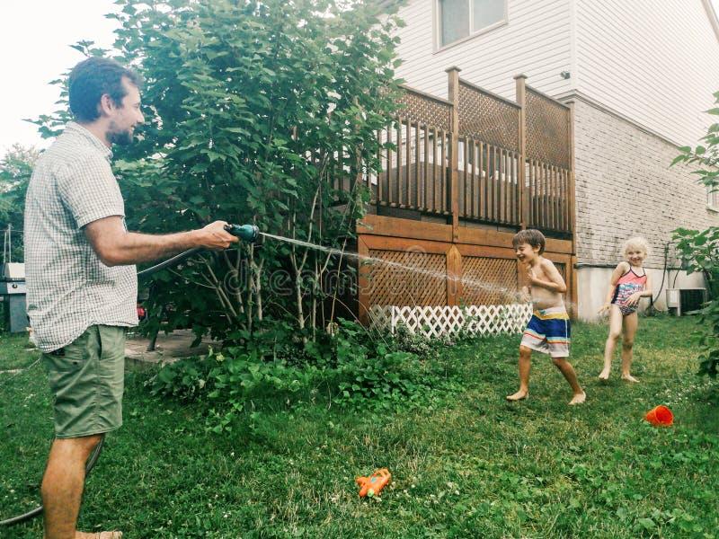 男孩飞溅使用的女友兄弟姐妹在水下在后院在热的夏日 免版税库存照片