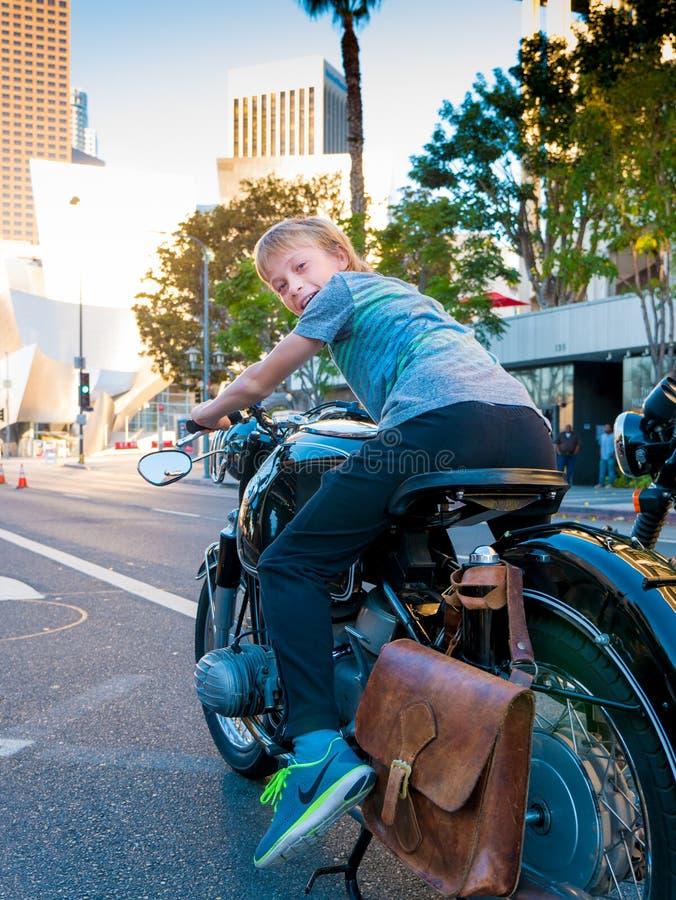 男孩骑马停放的葡萄酒摩托车在街市洛杉矶 库存照片