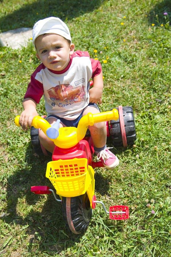 男孩骑马小孩三轮车 免版税库存图片