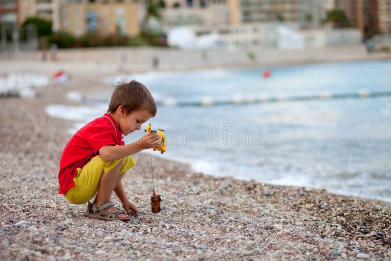 男孩,使用在海滩在雨以后的晚上与玩具 免版税图库摄影