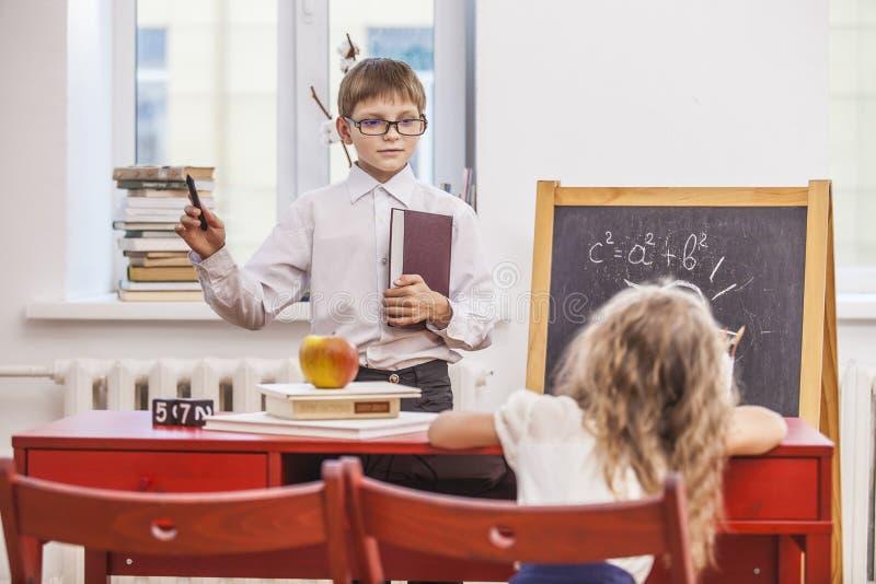 男孩,女孩孩子在学校有一愉快,好奇,聪明 免版税库存照片