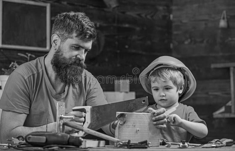 男孩,孩子繁忙在防护盔甲学会使用有爸爸的手锯 生,做父母与教小儿子的胡子 免版税图库摄影