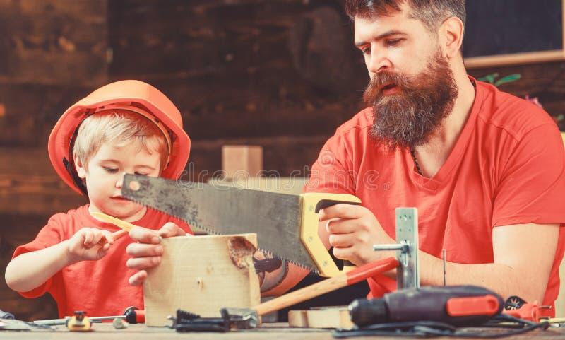 男孩,孩子繁忙在防护盔甲学会使用有爸爸的手锯 男性责任概念 父亲,父母与 免版税库存照片