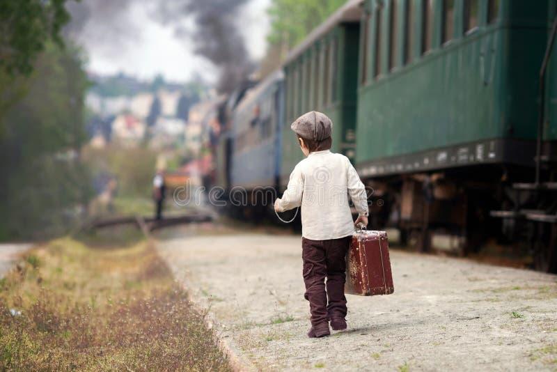 男孩,打扮在葡萄酒衬衣和帽子,带着手提箱 免版税库存照片