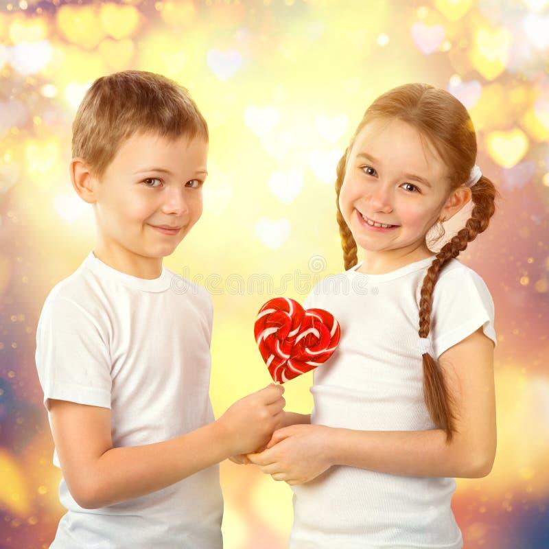 男孩给一个小女孩糖果在心脏形状的红色棒棒糖 华伦泰` s天艺术画象 免版税库存图片