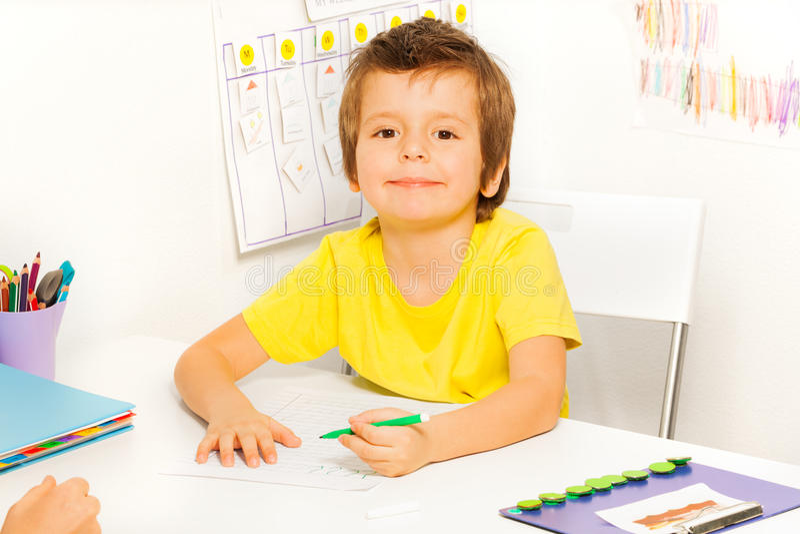 男孩画与笔在坐期间在桌上 图库摄影