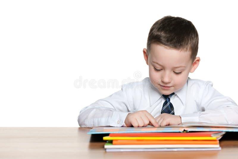 年轻男孩读在书桌 库存照片