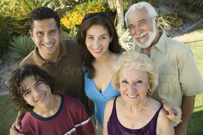 男孩(13-15)有父母和祖父母的在高的看法画象之外。 免版税库存照片